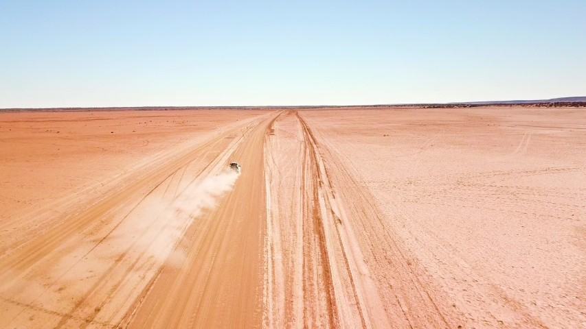 Aerial shot following a car stirring up a large dust cloud as it speeds along a dusty desert road. | Shutterstock HD Video #1032903104