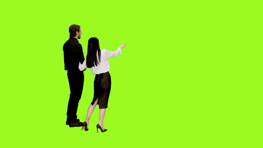 A beautiful couple, handsome man and seductive girl in love walking holding hands and looking at something on green screen background, Rear view, Chroma key, 4k shot