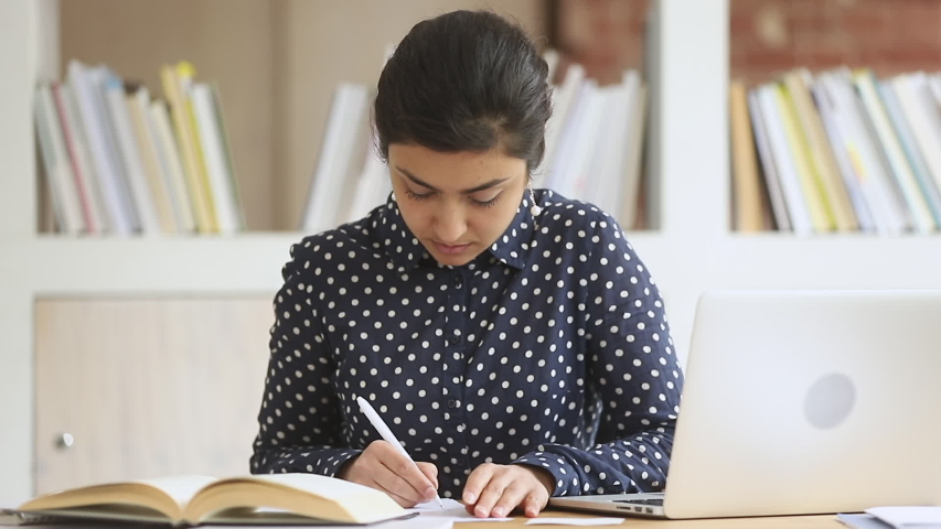 Focused smart indian ethnic girl college university high school student write notes essay homework assignment with textbook using laptop computer study in library prepare for exam sit at desk Royalty-Free Stock Footage #1032911057
