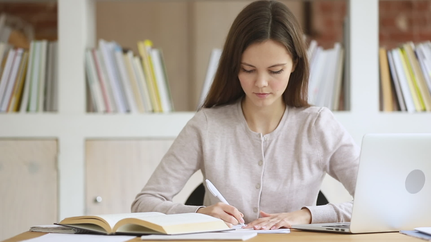 Smart girl college university school student write summary essay homework assignment with textbook study in library with laptop read book make notes learn literature prepare for exam sit at desk Royalty-Free Stock Footage #1032911066