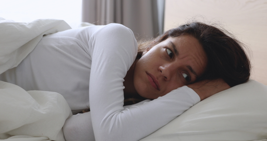 Frustrated upset young woman lying awake in bed alone trying to sleep suffer from insomnia or uncomfortable bad mattress, annoyed stressed lady insomniac feeling disturbed toss and turn in bedroom | Shutterstock HD Video #1032911081