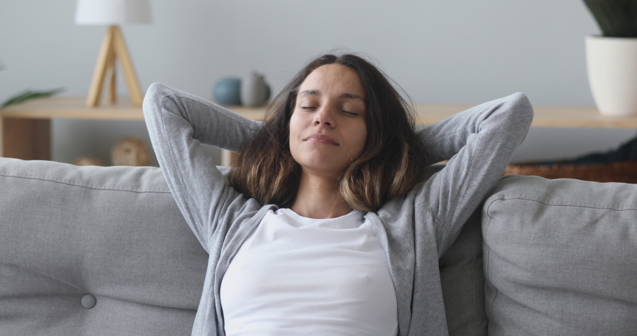 Calm serene young woman relax with eyes closed breathing fresh air napping lean on couch in living room, healthy mindful girl rest on sofa enjoy sleep feel stress relief peace of mind lounge at home | Shutterstock HD Video #1032911123