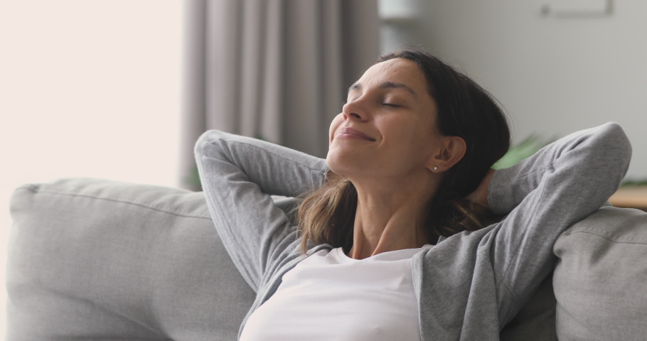 Happy relaxed young woman rest lounge lean on couch enjoy peaceful mood, healthy lazy calm girl dreaming breathing fresh air sit on comfortable sofa in living room on stress free cozy day at home