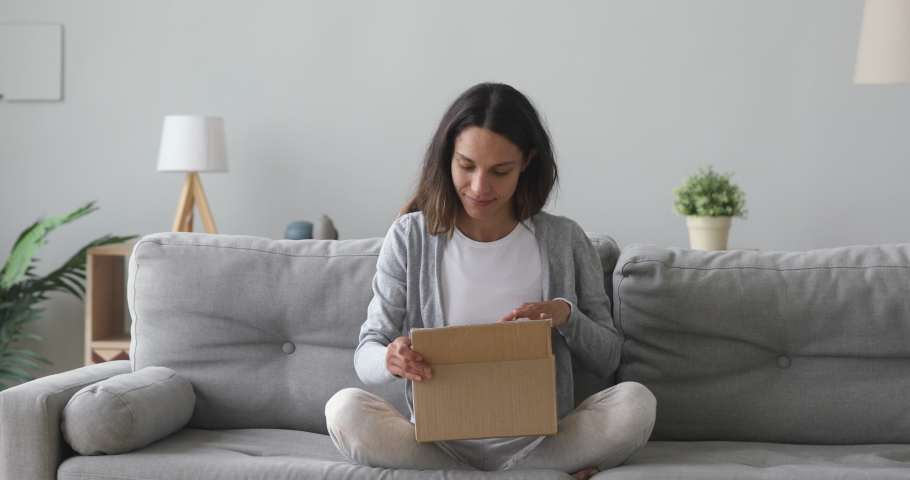 Happy young woman customer sit on sofa open parcel carton box satisfied with online shop order delivery at home, smiling girl consumer unpack package receive good purchase by postal shipping concept Royalty-Free Stock Footage #1032911129