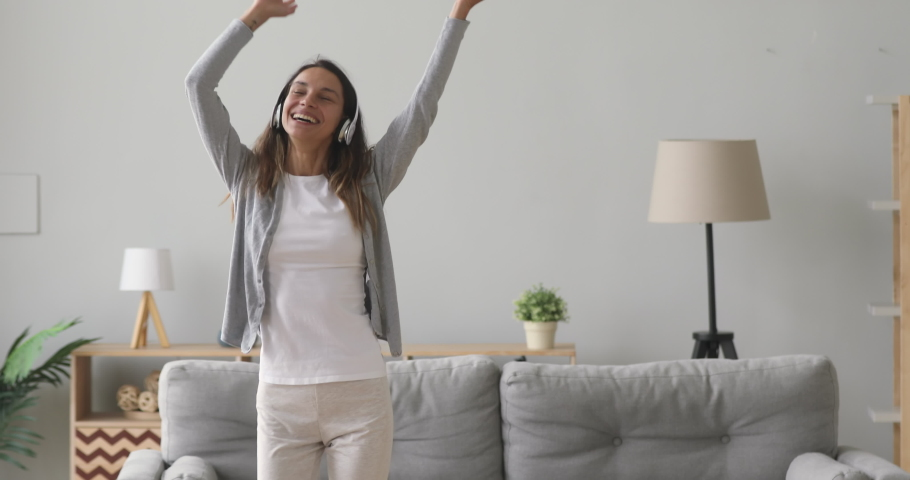 Happy carefree young woman wear wireless headphones dancing alone in modern living room, funny active teen girl jumping moving laughing at home listening to music enjoying new hit song having fun | Shutterstock HD Video #1032911159