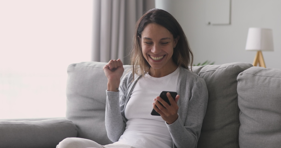 Happy overjoyed girl holding phone celebrate good mobile news surprise bid win game app victory sit on sofa at home, excited young woman winner screaming yes rejoicing success looking at cellphone Royalty-Free Stock Footage #1032911165