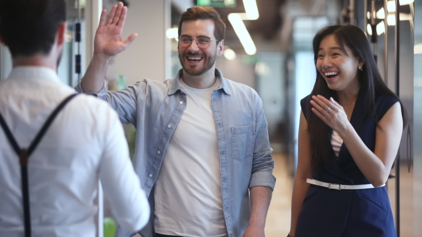 Happy diverse colleagues greeting talking standing in office hall, smiling multiethnic staff professional people giving high five chatting laughing enjoy friendly conversation meeting in work space