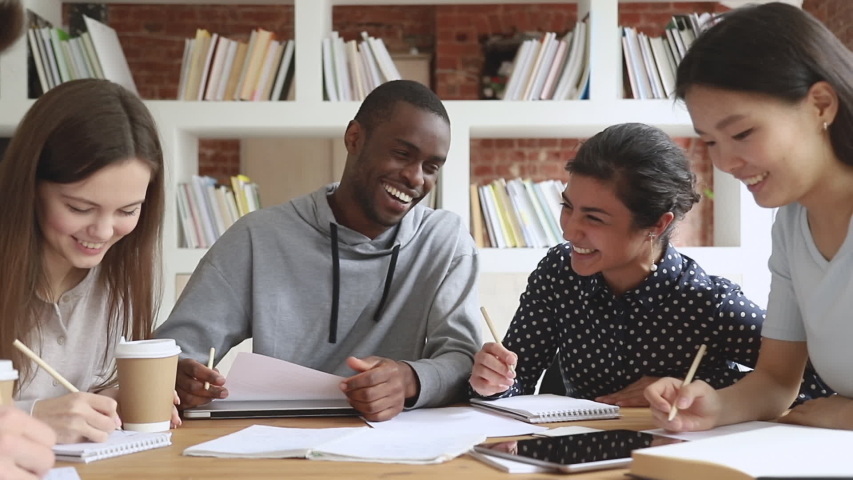 Cheerful multiethnic university college students team laugh at funny joke study together sit at table, happy diverse teen friends group having fun write homework work on project research in library Royalty-Free Stock Footage #1032911252