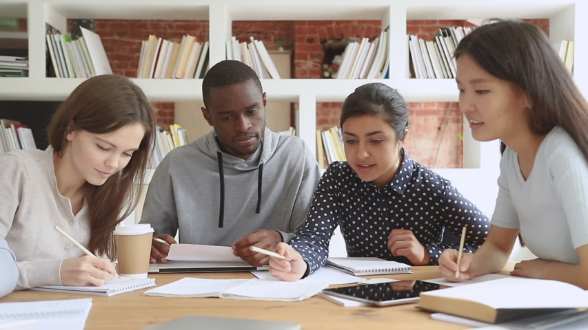 Multiracial college university students group study together prepare project make notes, happy diverse young people team write essay summary learn in teamwork do creative research homework in library Royalty-Free Stock Footage #1032911255