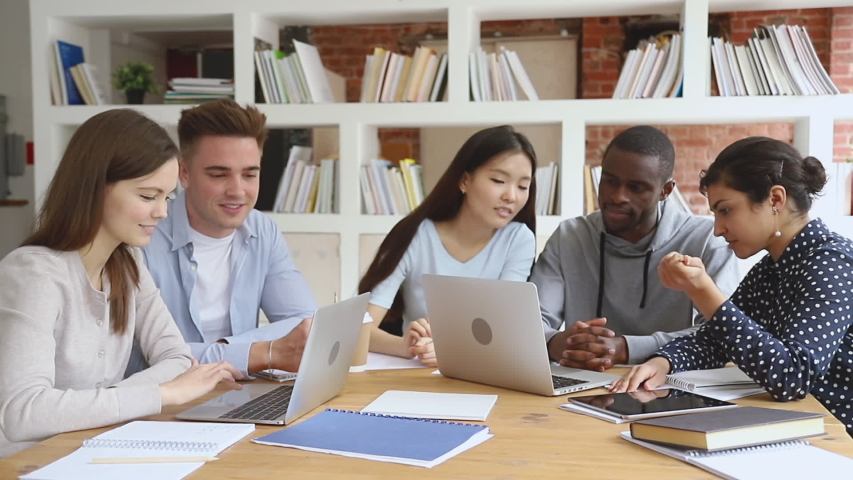 Focused diverse college university students team study together using laptop prepare for exam in library, multiethnic young people group talk looking at computer do online research project assignment Royalty-Free Stock Footage #1032911258