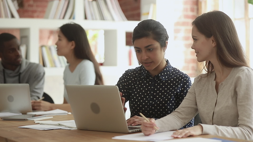 Focused indian young female teacher help caucasian friend student explain computer online project sit at desk in library, mentor teach intern, diverse university team girls learners study together Royalty-Free Stock Footage #1032911285