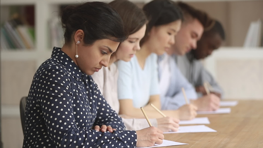 Focused serious female indian college uni student sit in row at desk with multiethnic people group writing test final exam answers or essay make notes on paper sheets pass examination concept Royalty-Free Stock Footage #1032911297