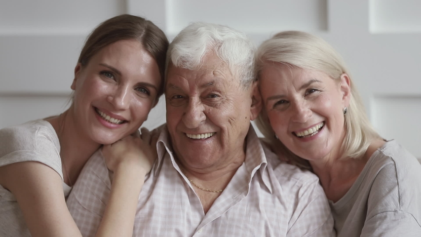 Happy family senior old parents and young adult daughter embracing bonding looking at camera, smiling elder grandparents mother father with grown granddaughter hugging cuddling, close up portrait