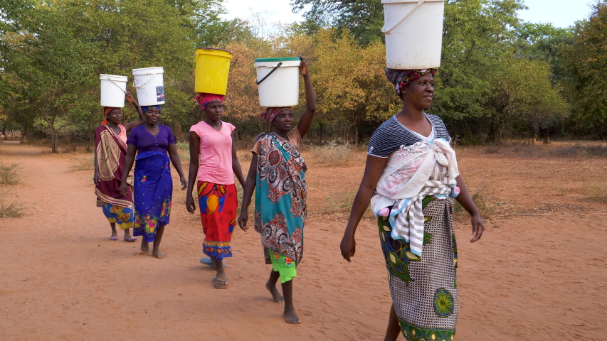 Poverty.Inequality.Poor people in Africa unable to maintain social distance due to water crisis. Five woman make the long journey home carry water in plastic containers on their heads