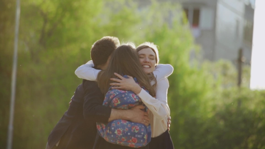 Happy schoolgirl running to her cheerful parents after lessons in the school courtyard. Lovely family hugs of parents and daughter. Royalty-Free Stock Footage #1032918200