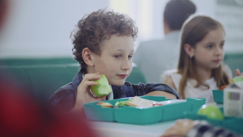 Funny and silly school children playing together and throwing food snacks in each other during break. Profile of smiling cute boy eating an apple by table. Royalty-Free Stock Footage #1032918224