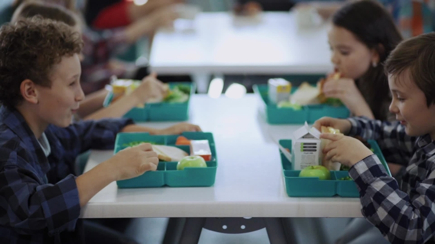 Cute elementary school children sitting by table eating their tasty snacks during lunch in cafeteria at school. Royalty-Free Stock Footage #1032918341