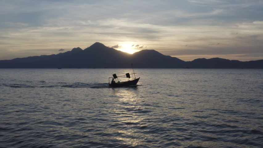 Fishing Boat motors out to ocean at sunset against a beautiful landscape in Asia #1032931592