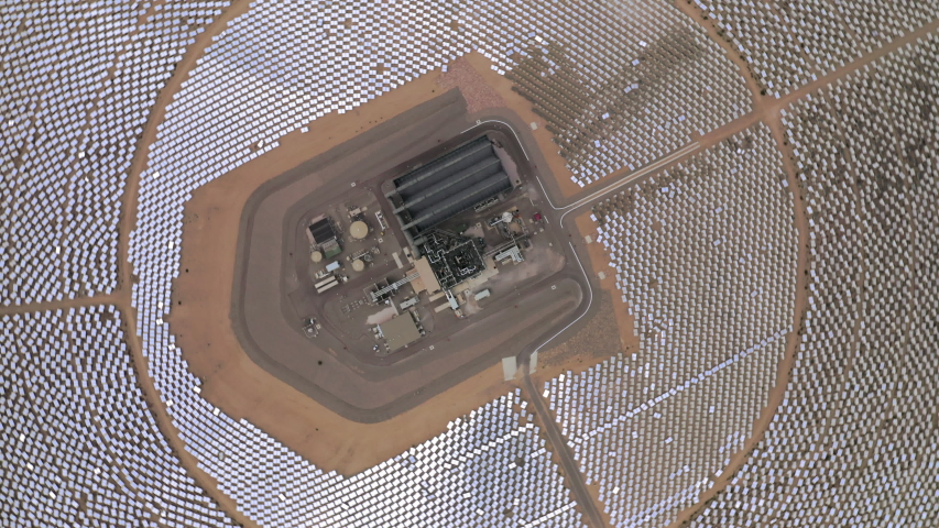 Drone rotates on its axis showing view on circles of solar panels and power station in the middle. Aerial 4K