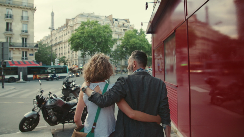 Healthy active elderly couple walk with their arms around eachother's shoulders in the bustling streets of Paris France