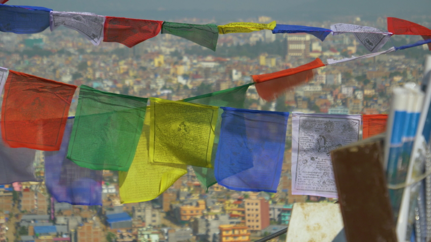 SLOW MOTION, CLOSE UP, DOF: Colorful prayer flags flutter over the city of Kathmandu in the background. Scenic shot of buddhist flags suspended from a Swayambhunath stupa moving in the autumn breeze. | Shutterstock HD Video #1032944279