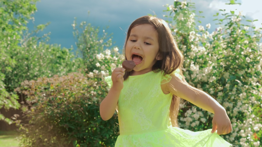 A little cute and funny girl in a bright green dress grimaces and eats chocolate ice cream. In the background is a natural public park or backyard of the house. #1032947324
