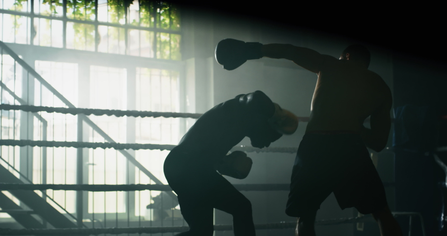 Cinematic slow motion shot of two professional young muscular shirtless male boxers are fighting and embracing after in a boxing ring.