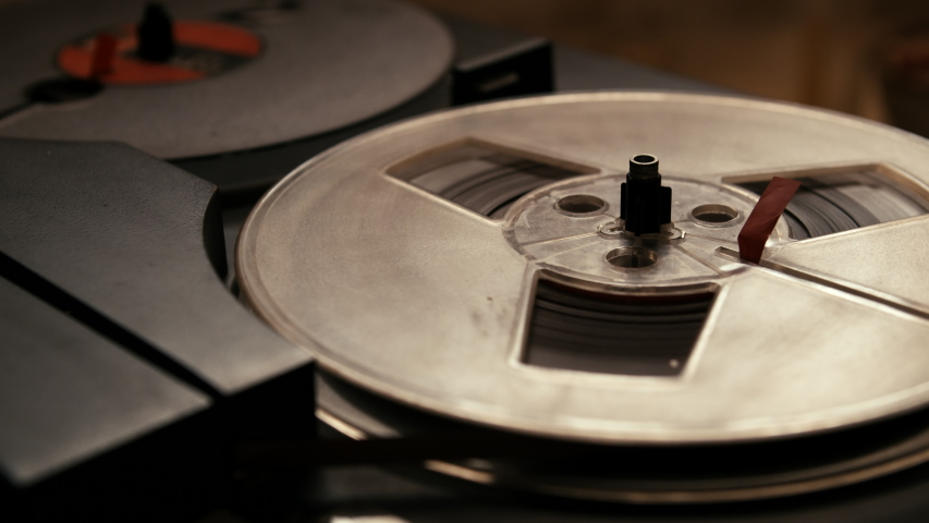 Close up shot of spinning takeup reel of old analog reel-to reel audio tape recorder, form of magnetic tape audio recorder in which the recording medium is held on a reel that is not in a cassette. | Shutterstock HD Video #1032956132