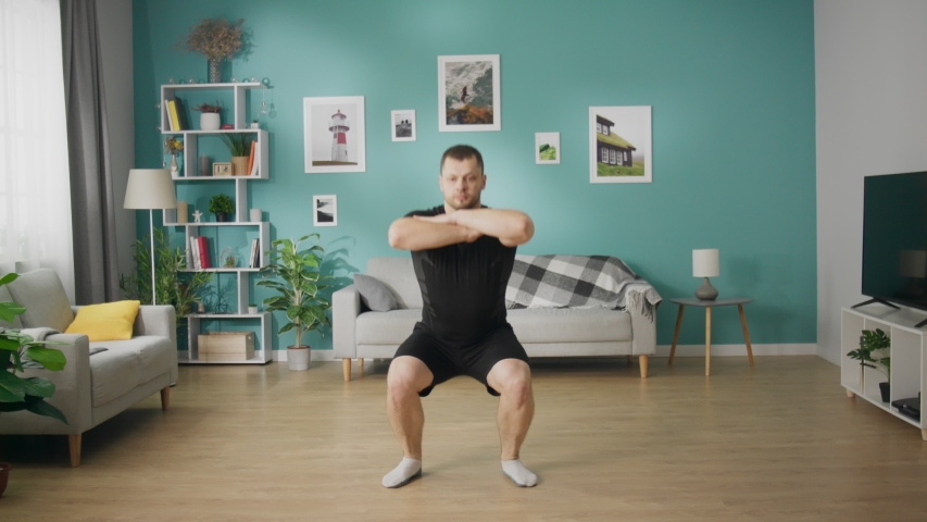 Young man is doing exercises on floor of modern apartment | Shutterstock HD Video #1032983129