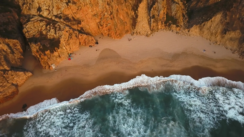 Top down view of waves breaking in the sand in Ursa Beach, Sintra, Portugal. A person running along the beach at sunset