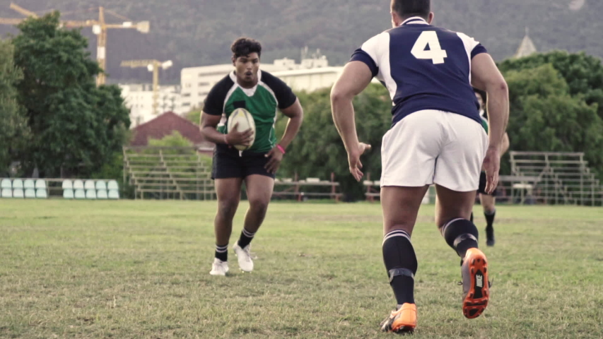 Rugby player tackling the opponent during the game. Rugby players fight for the ball on the field.