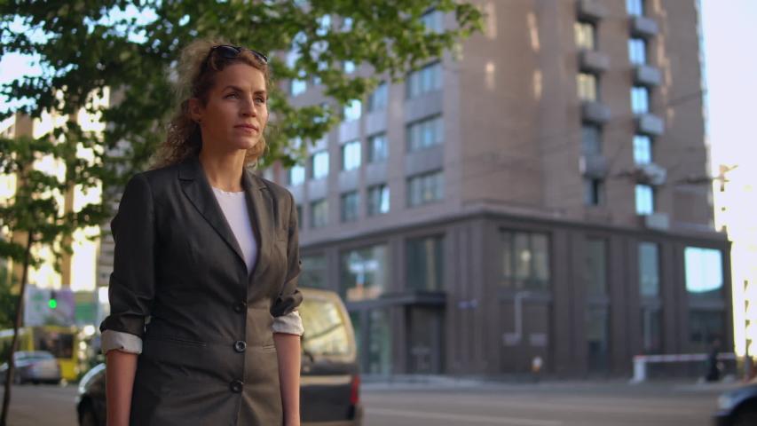 Adult beautiful woman walking on the street in early morning. caucasian businesswoman wearing elegant jacket going to work   Shutterstock HD Video #1033001384