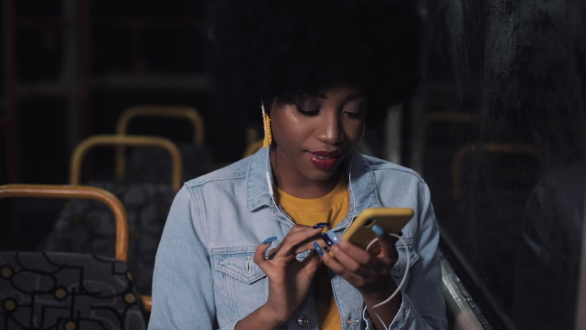 Attractive young african american woman using smartphone riding at public transport. Night time. City lights background. | Shutterstock HD Video #1033017404