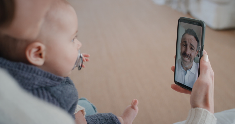 Mother and baby using smartphone having video chat with father waving at infant on screen enjoying communicating with family on mobile phone connection 4k