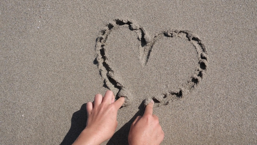 Heart written in sand on the beach is washed away by sea waves. Shooting on the beach. Ultra HD H.264