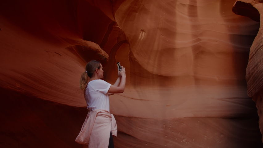 Caucasian female taking pictures with her phone in Antelope Canyon, Arizona. 4K UHD RAW edited footage