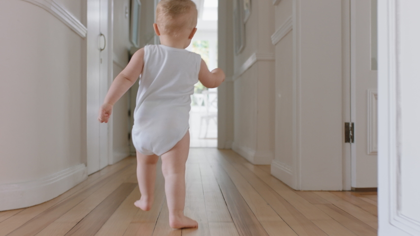 baby boy learning to walk toddler exploring home curious infant walking through house enjoying childhood