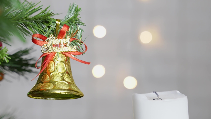 Hand with a match lights a candle next to a fir branch with a Christmas toy. | Shutterstock HD Video #1033045580