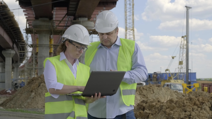 man and woman working on construction site. manager and architect discuss future installation plan for construction of overpass using laptop. #1033045586
