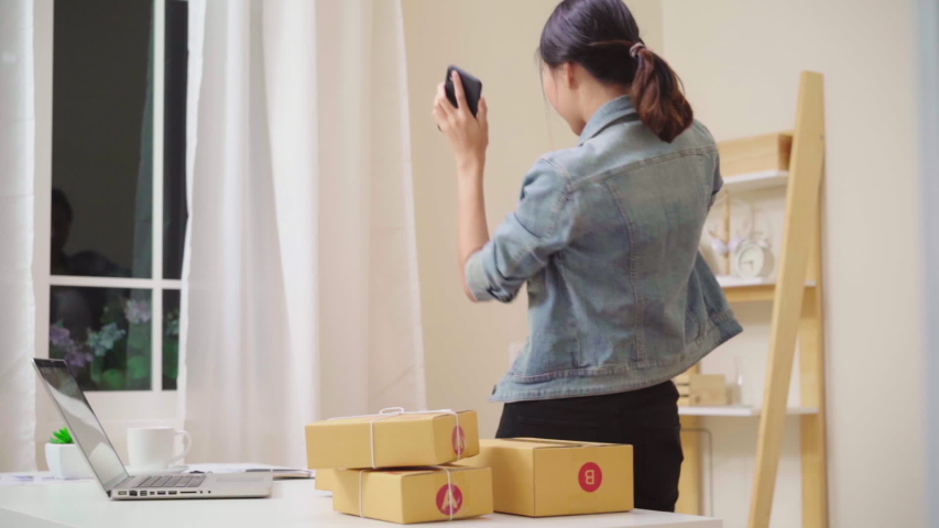 Asian young woman checking product on stock and save to laptop working at house. female entrepreneur business owner of SME happy dancing according rhythm song, relax after work at home. Slow motion.   Shutterstock HD Video #1033046981