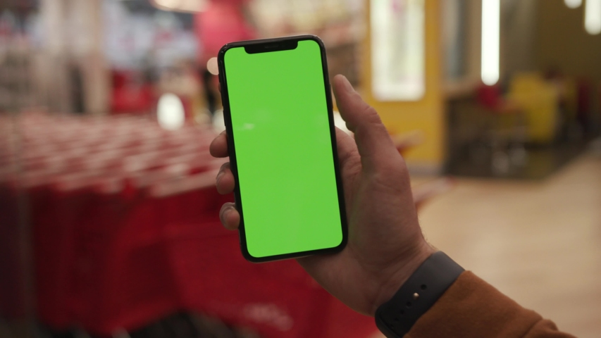 NEW YORK - April 19, 2019: Man hands holding use iPhone with vertical green screen on night city colorful light background  | Shutterstock HD Video #1033059167
