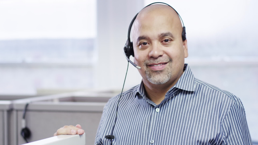 Smiling Hispanic businessman leaning on cubicle posing with headset