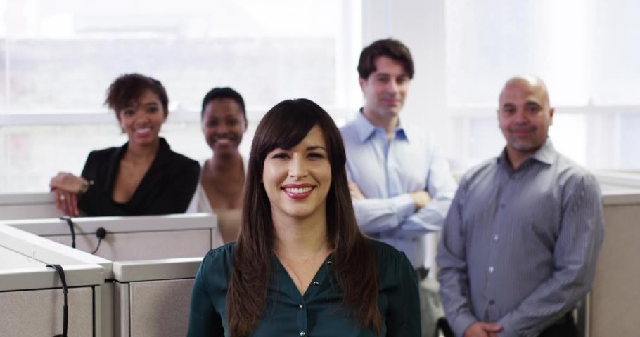 Smiling business people posing in cubicles