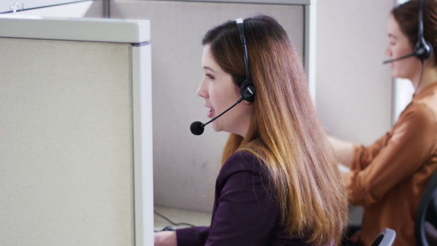 Businesswomen talking on headsets in call center cubicles
