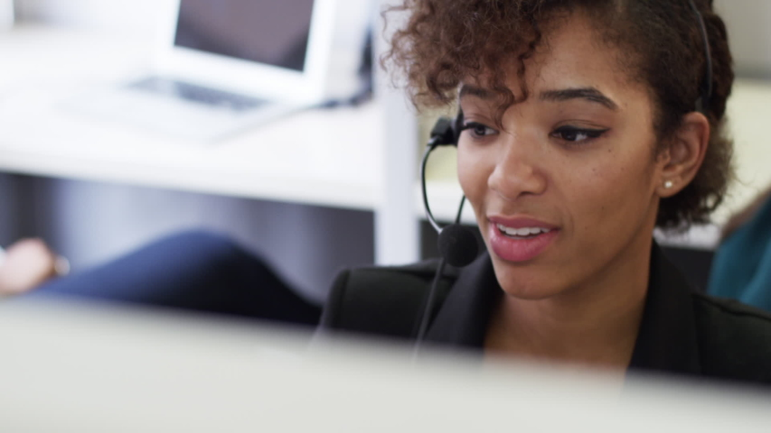 Businesswoman talking on headset sitting in cubicle