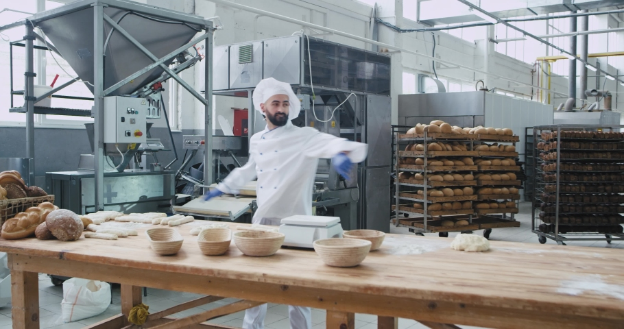 Dancing excited man baker in the kitchen bakery at his working table enjoying the time at work , while preparing dough forming pieces