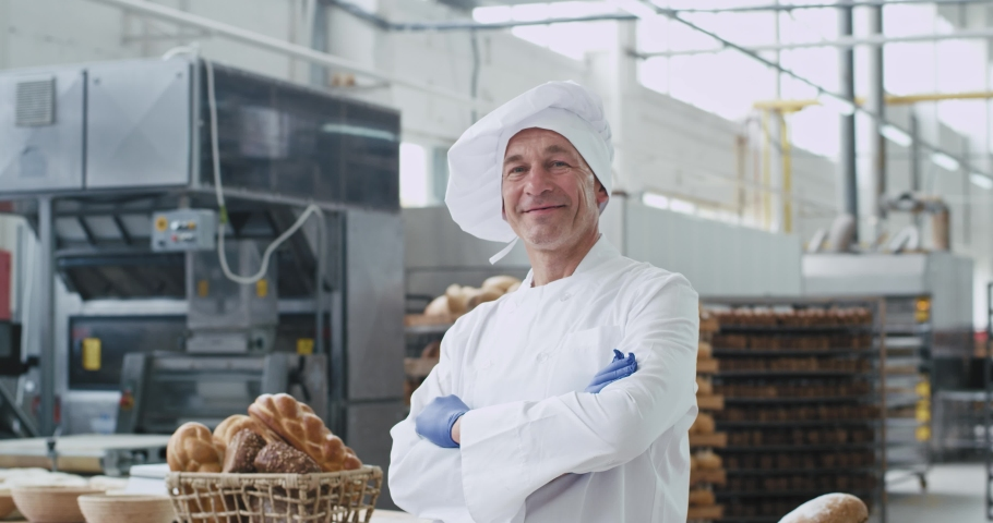 Old man baker portrait looking straight to the camera in a big bakery industry he enjoying the time at his work place