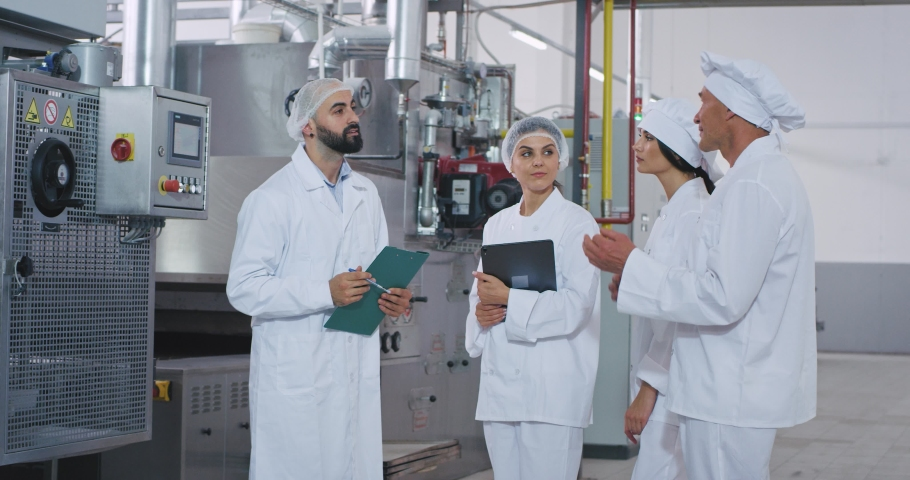 Baker chef old man and young engineer guy with beard have a conversation with their assistance in the middle of bakery industry factory