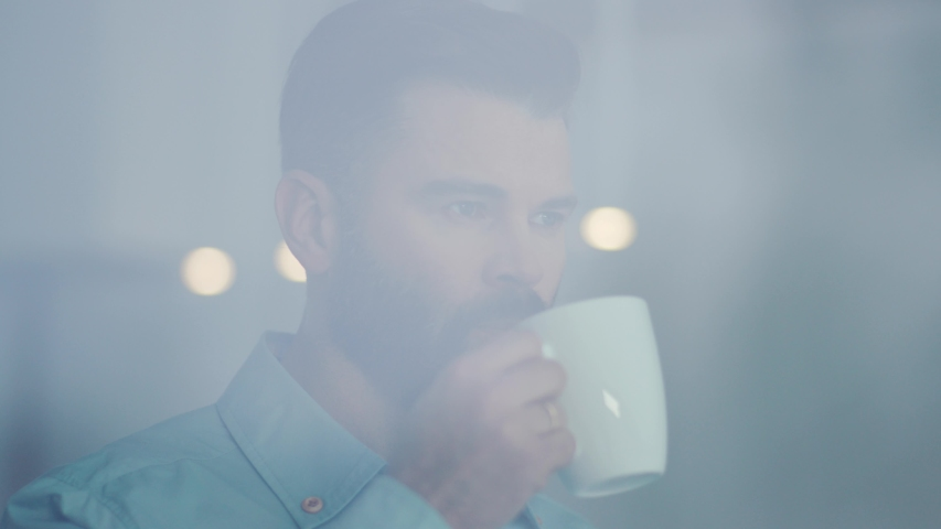 Young businessman drinking coffee and admire view standing by window in office