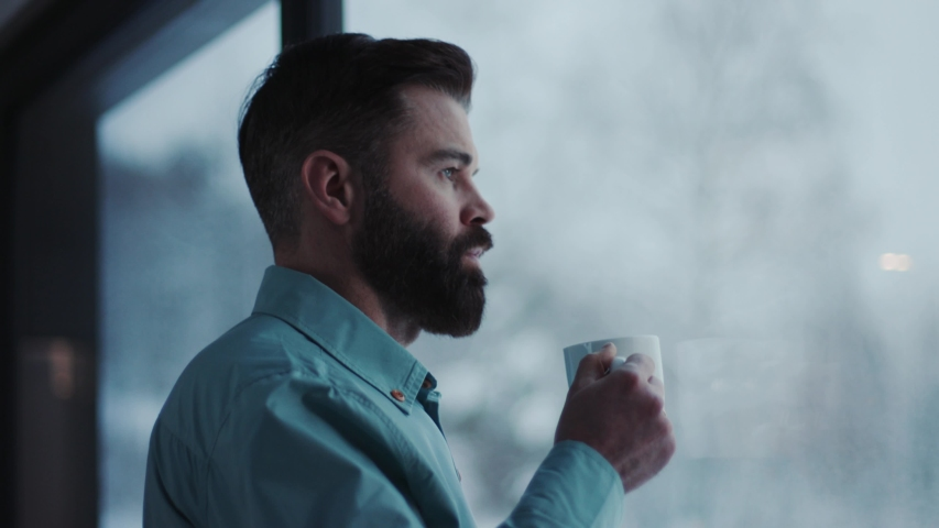 Close up handsome businessman drinking coffee and admire view standing by window in office